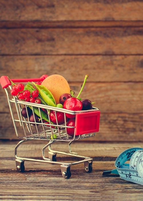 Kleiner Einkaufswagen gefüllt mit Obst und Gemüse , daneben ein Maßband