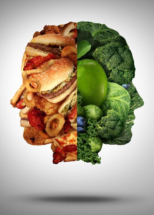 Gesicht geformt auf einer Seite aus Gemüse auf der anderen aus Fastfood