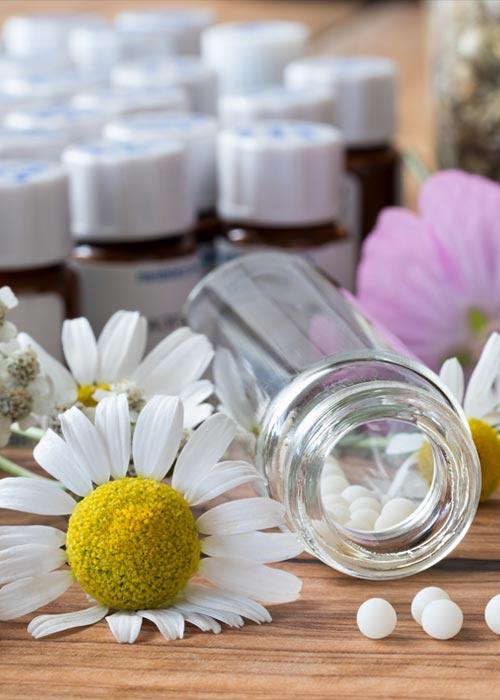 auf einem Tisch liegen ein homöopatische Pastillen neben einer Kamillenblüte