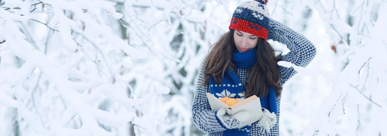 Frau im Schnee mit einem Buch in der Hand.