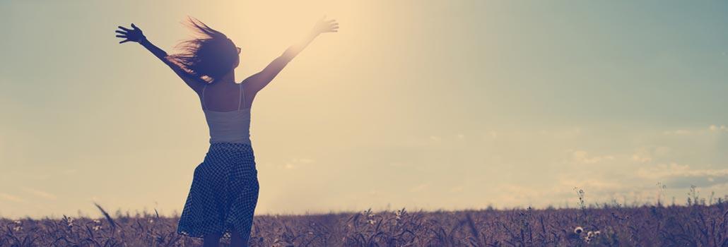 Eine junge Frau im Sonnengang auf einer Wiese stehend, die Arme ausgebreitet