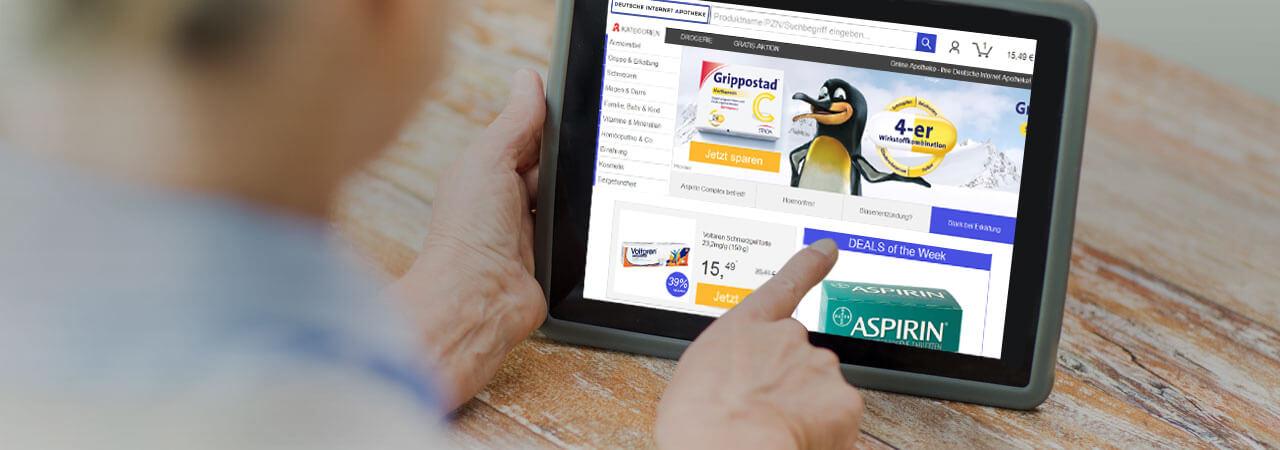 Mann liegt auf dem Boden und schaut sich die Webiste der Deutschen Internet Apotheke auf seinem Tablet an