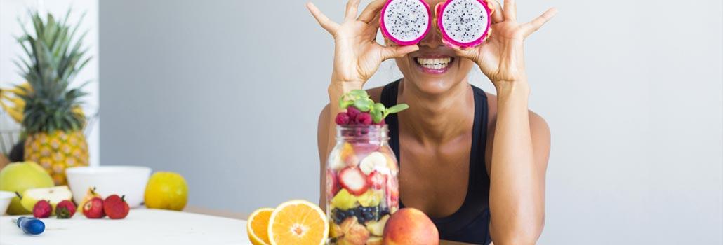 Eine Frau, die Obstscheiben vor ihren Augen hält, sitzt an einem Tisch, bedeckt mit verschiedenen Früchten