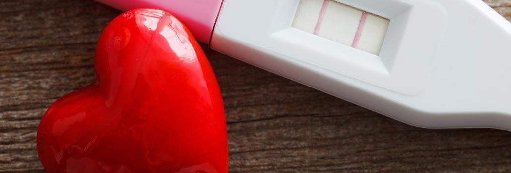 Ein Schwangerschaftstest, davor ein Herz