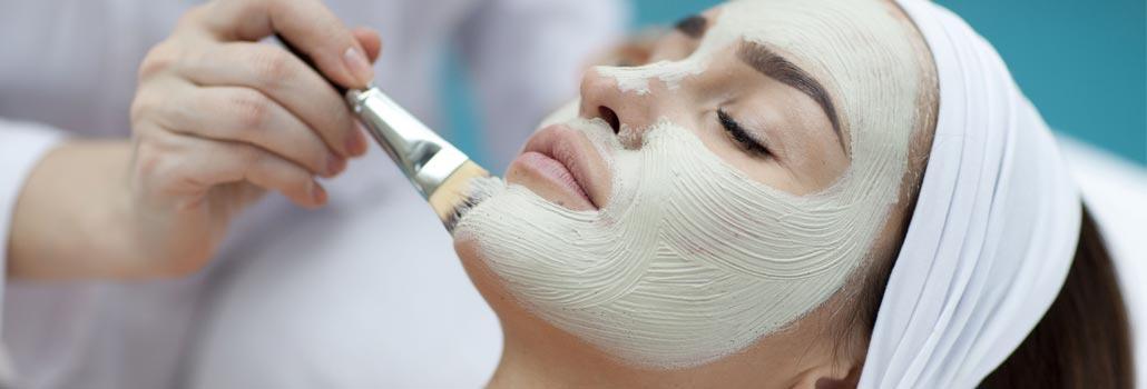 Gesicht einer jungen Frau, die mit einem Pinsel eine Maske aufgetragen bekommt
