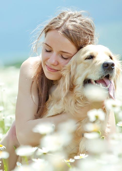 Frau kuschelt mit ihrem Hund auf einer Wiese